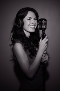Attractive brunette woman recording a song in music studio. Black and white photo.